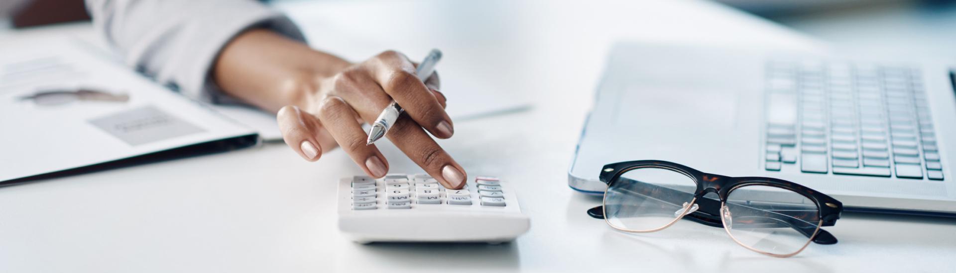 Businesswoman using a calculator at her desk