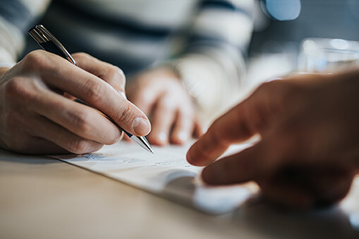 Man signing a contract while advisor is aiming at the place he need to sign.